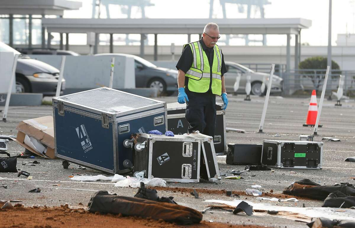 A CHP accident investigator walks through debris strewn across westbound traffic lanes at the Bay Bridge toll plaza after a truck rammed through toll booth 14, killing the toll collector inside, before dawn in Oakland, Calif. on Saturday, Dec. 2, 2017. The two occupants of the truck were reportedly ejected from the vehicle.