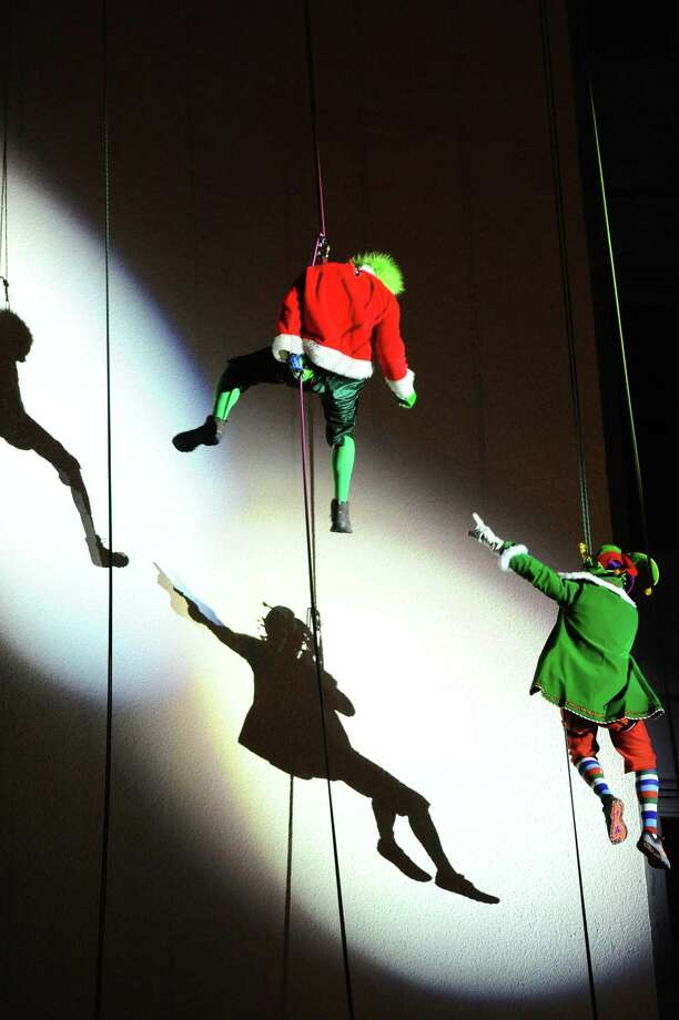 Yankees General Manager Brian Cashman, dressed as an elf, fights Jason Teitelbaum, dressed as the Grinch, while rappelling down the Landmark Building during the 2016 Heights & Lights Rappel in Stamford, Conn. on Sunday, Dec. 4, 2016. The annual holiday tradition returns to Stamford's Landmark Square Sunday at 5 p.m. Photo: Michael Cummo / Hearst Connecticut Media / Stamford Advocate