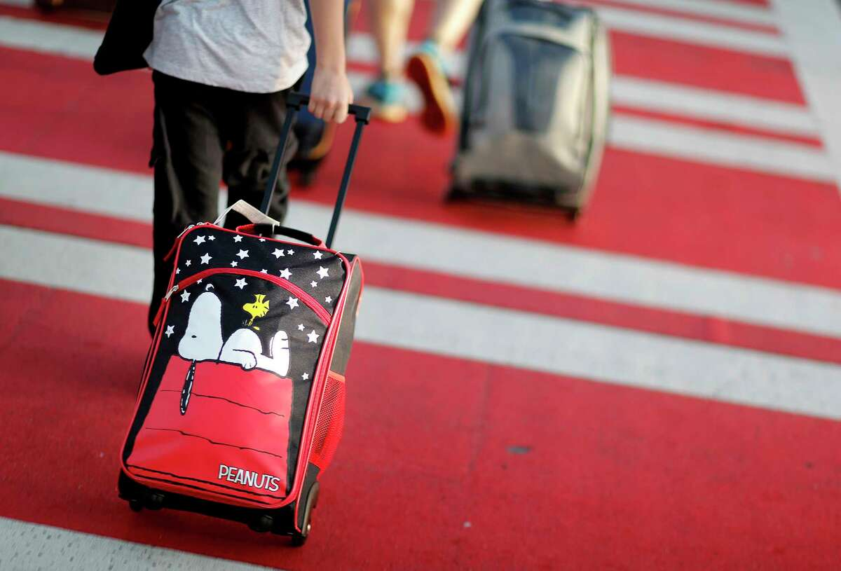 FILE - In this Wednesday, Nov. 22, 2017, file photo, a child pulls a suitcase along a crosswalk upon arriving at Hartsfield-Jackson Atlanta International Airport ahead of the Thanksgiving holiday in Atlanta. It?'s getting late for booking holiday travel, but not too late. Experts say there are tips for procrastinators to find affordable airfares and hotel rooms. Flexibility is the key. (AP Photo/David Goldman, File) ORG XMIT: NYBZ412