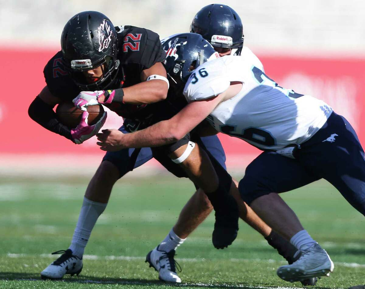 Kingwood's Travis Kent, right, tackles Langham Creek's Timothy Knapp during the fourth quarter of the Class 6A Division 2 Region 3 playoffs game at TDECU Stadium on Saturday, Dec. 2, 2017, in Houston. The Langham Creek Lobos defeated Kingwood Mustangs 51-16.