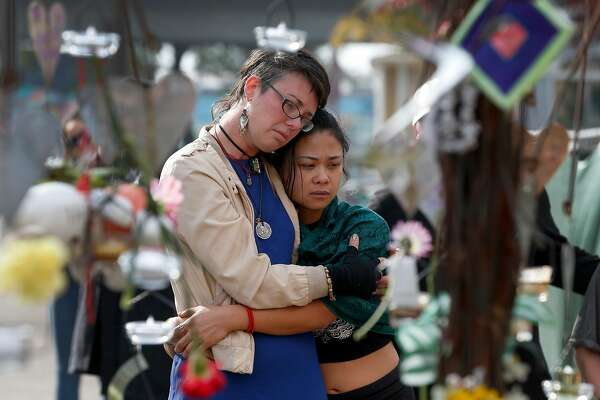 Kelly Jewett (left) and Ani Sabillo embrace as they mourn friends who died at the Ghost Ship warehouse during a memorial service in Oakland, Calif. on Saturday, Dec. 2, 2017 to mark the one-year anniversary of the fire where 36 people were killed.