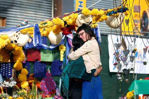 Ani Sabillo (left) and Kelly Jewett embrace as they mourn friends who died at the Ghost Ship warehouse during a memorial service in Oakland, Calif. on Saturday, Dec. 2, 2017 to mark the one-year anniversary of the fire where 36 people were killed.
