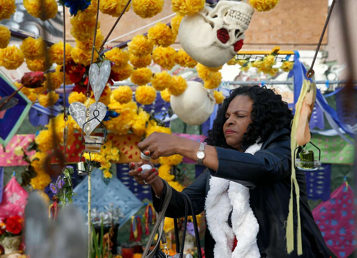 Louisette Cameau arranges a memorial in front of the Ghost Ship warehouse in Oakland, Calif. on Saturday, Dec. 2, 2017 to mark the one-year anniversary of the blaze that killed 36 people.