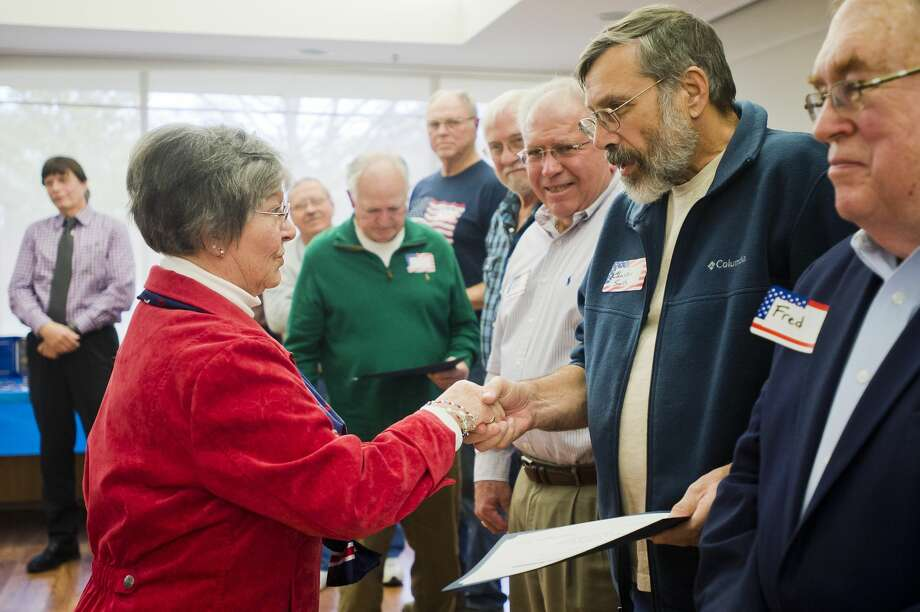 Carolyn Graham, regent of the John Alden chapter of the Daughters of the American Revolution, hands a certificate and a pin to Charles Smith, who served in the Vietnam War, during an event commemorating Vietnam veterans on Friday at the Greater Midland Community Center. (Katy Kildee/kkildee@mdn.net) Photo: (Katy Kildee/kkildee@mdn.net)