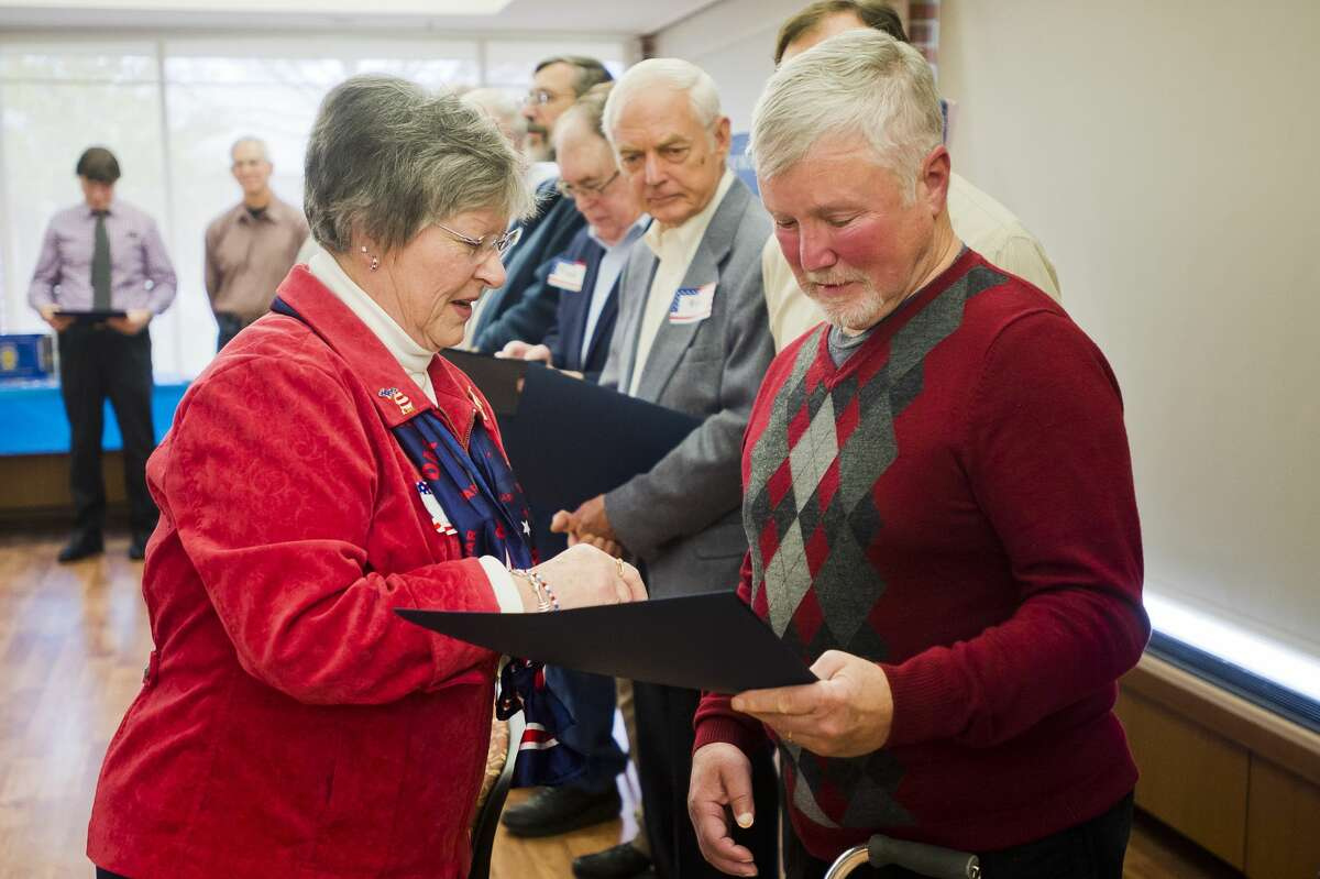 Carolyn Graham, regent of the John Alden chapter of the Daughters of the American Revolution, hands a certificate and a pin to Ken Pegovskie, who served in the Vietnam War, during an event commemorating Vietnam veterans on Friday at the Greater Midland Community Center. (Katy Kildee/kkildee@mdn.net)