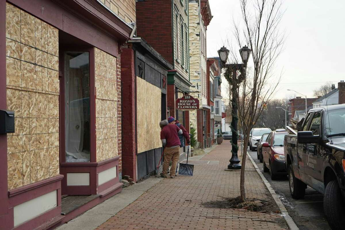 Passersby observe the aftermath of the massive fire that tore through downtown Cohoes on Nov. 30, 2017. (Massarah Mikati/Times Union)