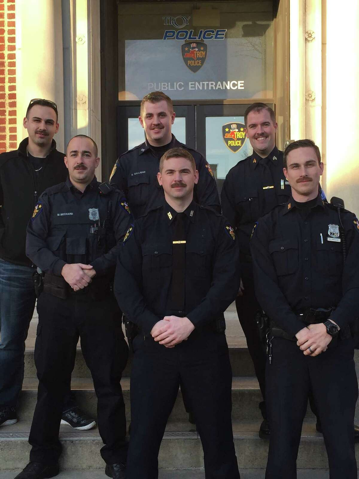 Six Troy police officers stand outside police headquarters sporting mustaches (well within department grooming policies) that they grew for a No Shave November effort to raise money for the Butler Foundation, which supports mesothelioma research. Standing from left in the back row are Officer Kevin Ray, Officer Brandon Galligan and Sgt. Steve Barker. Bottom row, from left, are officers Mike Bechard, Owen Conway and Eric Radigan. They raised $200 plus a match by the Troy Police Benevolent Association to give $400 to the foundation. (Photo provided)