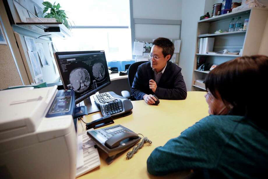 Alison Cairnes, right, looks at images with her doctor, Shumei Kato, at the University of California in San Diego. Tumor profiling Cairnes' cancer genes helped Kato identify an effective treatment for her gastric cancer. Photo: Gregory Bull, STF / Copyright 2017 The Associated Press. All rights reserved.