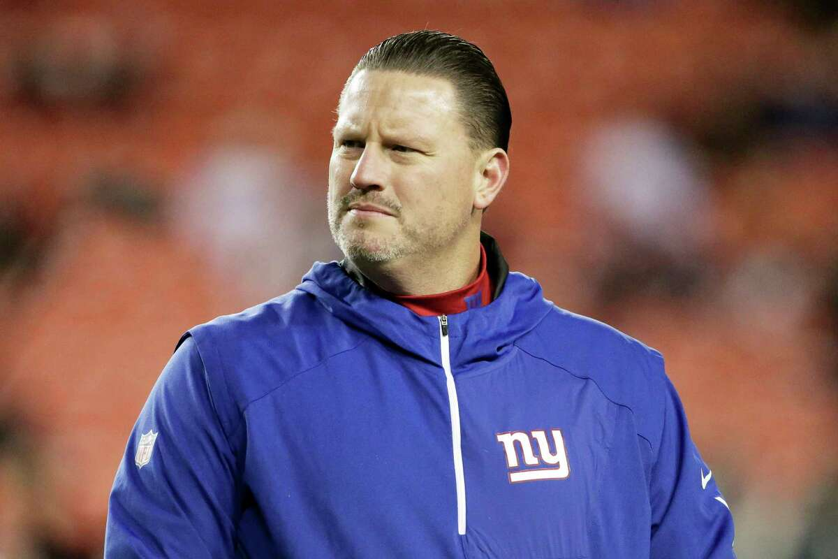 """FILE - In this Nov. 23, 2017, file photo, New York Giants coach Ben McAdoo stands on the field before the team's NFL football game against the Washington Redskins in Landover, Md. The Giants have little to play for and have already started planning for the future by benching two-time Super Bowl winning quarterback Eli Manning in order to get the opportunity to take a look at Geno Smith on Sunday against the Raiders and rookie Davis Webb down the road. It's a decision that was extremely unpopular in New York among fans who remember Manning's Super Bowl success and former players upset about the treatment of one of the franchise's most important players. """"The decision is bigger than me. It's for the organization and the future of the organization, making sure we have a clear evaluation of the other two quarterbacks on the roster,"""" McAdoo said. (AP Photo/Mark Tenally, File) ORG XMIT: NY161"""