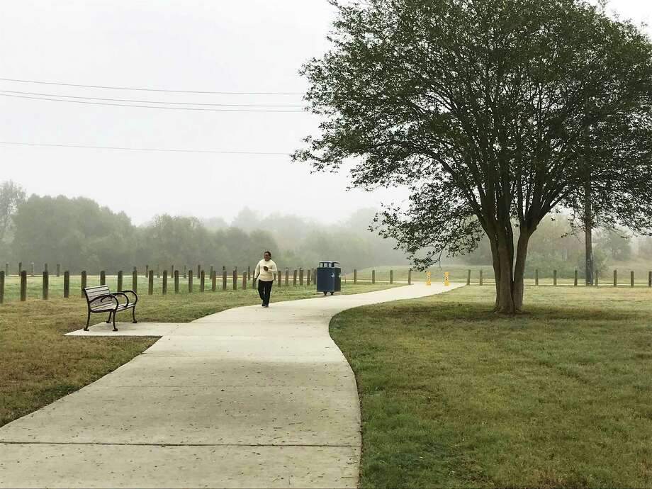 Maria Gomez strolls along a path created by the Houston Parks Board across a new green space that was formerly the site of the crime-ridden, abandoned Oakbrook Apartments on De Soto Street in northwest Houston. Photo: Molly Glentzer
