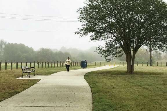 Maria Gomez strolls along a path created by the Houston Parks Board across a new green space that was formerly the site of the crime-ridden, abandoned Oakbrook Apartments on De Soto Street in northwest Houston.