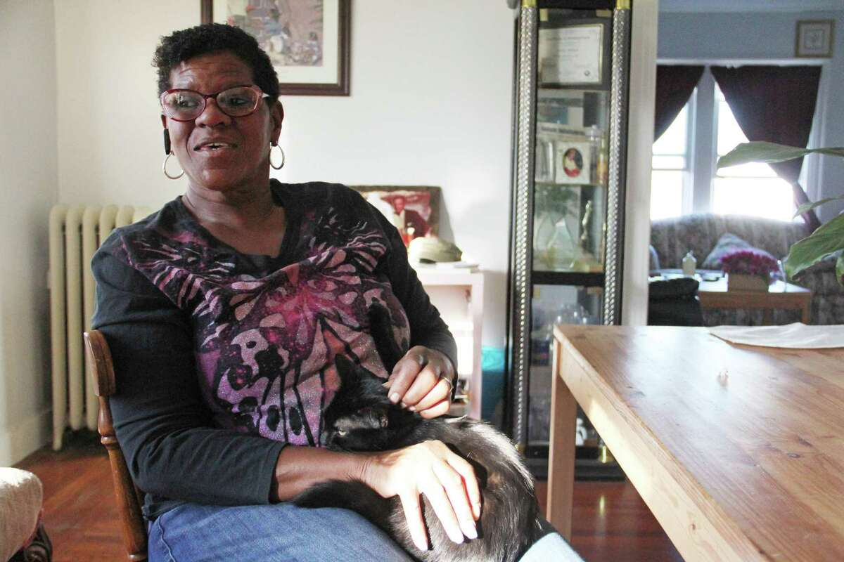 Kimberly Hart sits with her cat, Midnight, inside her home on Friday, Dec. 1, on Sherman Avenue in New Haven. Hart is on the New Haven Food Policy Council, which works to address food insecurity concerns in the community.