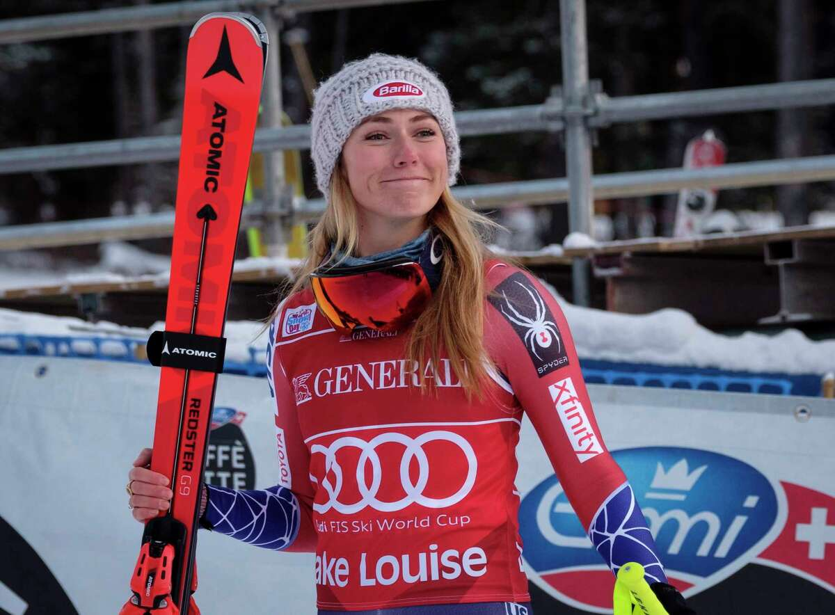 Mikaela Shiffrin, of the United States, celebrates her victory as she walks to the podium following the women's World Cup downhill skiing action in Lake Louise, Alberta, Saturday, Dec. 2, 2017. (Jeff McIntosh/The Canadian Press via AP) ORG XMIT: JMC120
