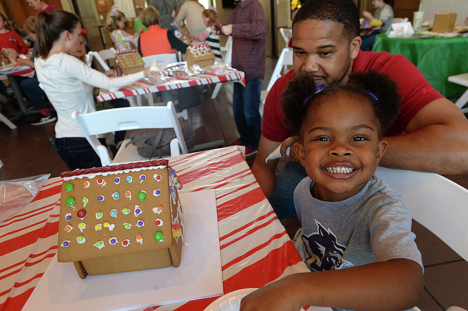 Sydney Petry smiles as she and father Aundrey join families taking part in the Art Museum of Southeast Texas' annual gingerbread house decorating event Saturday. Photo taken Saturday, December 2, 2017 Kim Brent/The Enterprise Photo: Kim Brent / BEN
