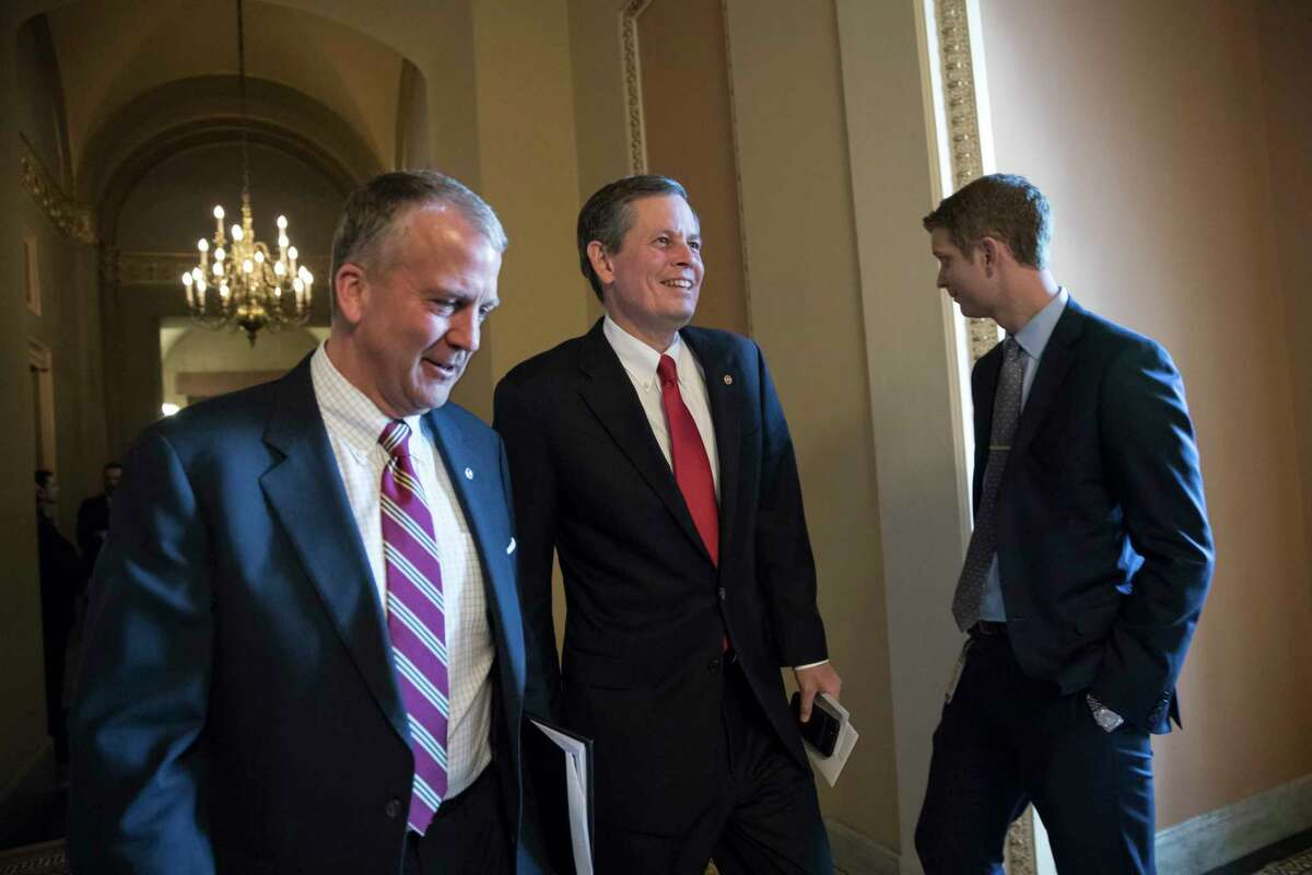 Sen. Dan Sullivan, R-Alaska, left, walks with Sen. Steve Daines, R-Mont., as they head to the Senate chamber after a closed-door meeting with Republican lawmakers to advance the GOP overhaul of the tax code, on Capitol Hill in Washington, Friday, Dec. 1, 2017. (AP Photo/J. Scott Applewhite) ORG XMIT: DCSA133