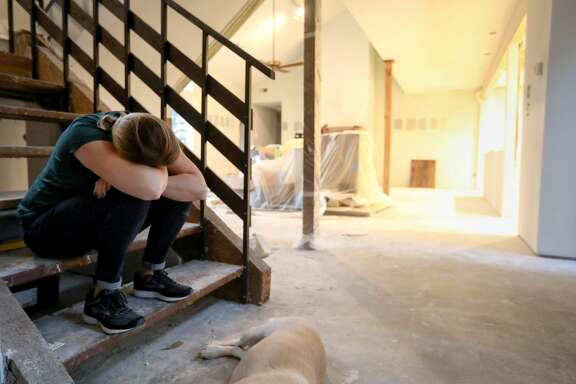 "Kate Thompson sits at the bottom of the stairs in her flood-damaged home, in Houston. Thompson was upset that day because a contractor had told her repairs would be finished in February. ""Even though the process is extremely frustrating, we just have to keep reminding ourselves that it could be a whole lot worse,"" she said."
