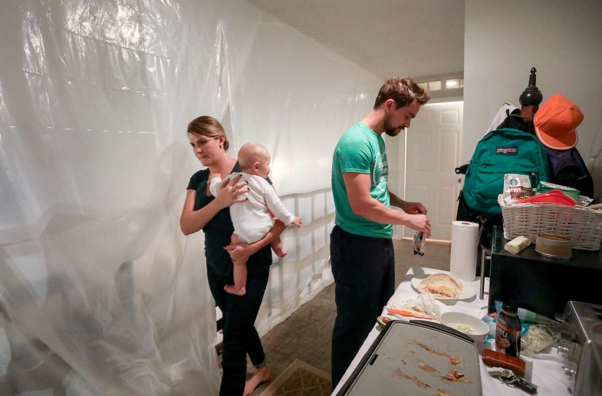 Henry Thompson cooks dinner for himself as his wife Kate carries their six-month-old son, Jack, to an upstairs room where the family spends most of their time at home, in Houston.