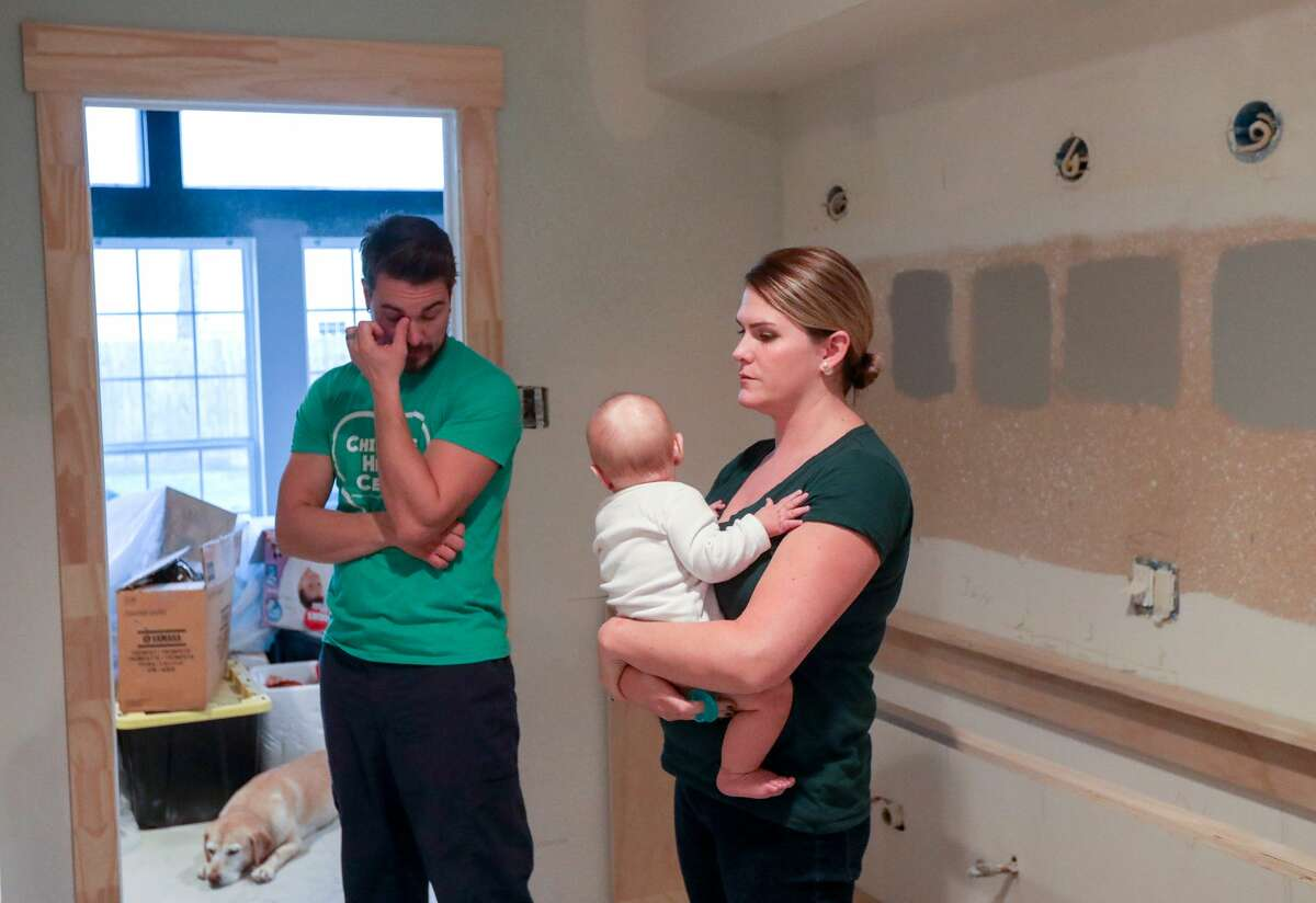Henry Thompson, from left, his six-month-old son Jack, and his wife Kate, talk about the progress of repairs on their home, in the Norchester neighborhood, in Houston.