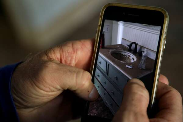 Todd Middleton shows a picture of flood-damage from Hurricane Harvey, in his home, in Houston.