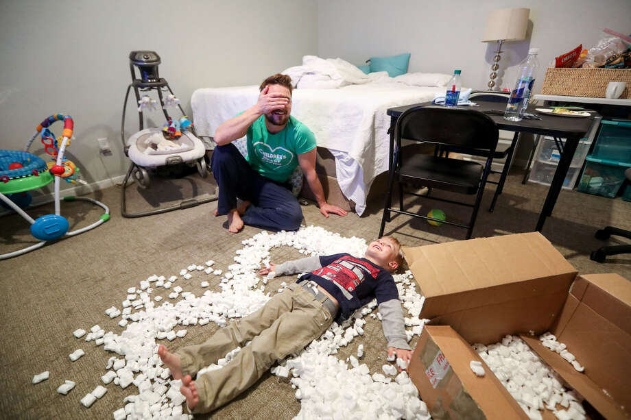 "Henry Thompson watches his son Harrison, 4, play in a box full of packing peanuts, in a second-floor bedroom of the family's flood-damaged home, in Houston. Thompson said the small room was where the family did almost everything. ""It's a bit of perspective for us,"" Thompson said. ""Everyone else on our street just did this 18 months ago."" Photo: Jon Shapley/Houston Chronicle"