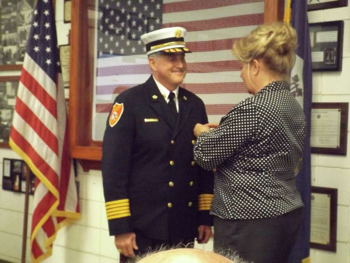 David Gallitto, fire commission chairman, administers the oath of office to Chief Michael Howley of Middletown?'s South Fire District and Loretta Howley pins her husband at his swearing in ceremony.
