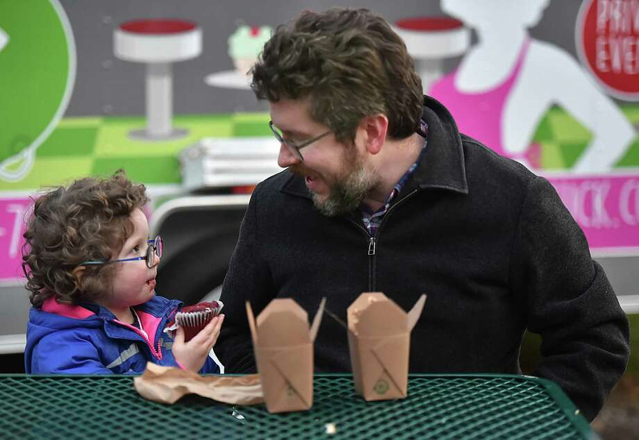 Hamden resident Ellery Frahm chats with his 4-year-old daughter Sylvia while she enjoys a Red Velvet Oreo cupcake at the food court, Saturday, Dec. 2, 2017 at the Hamden annual Silverbells Holiday Festival, an annual outdoor celebration sponsored by the Hamden Arts Commission and the Department of Arts & Culture at Town Center Park in Hamden. Photo: Catherine Avalone, Hearst Connecticut Media / New Haven Register