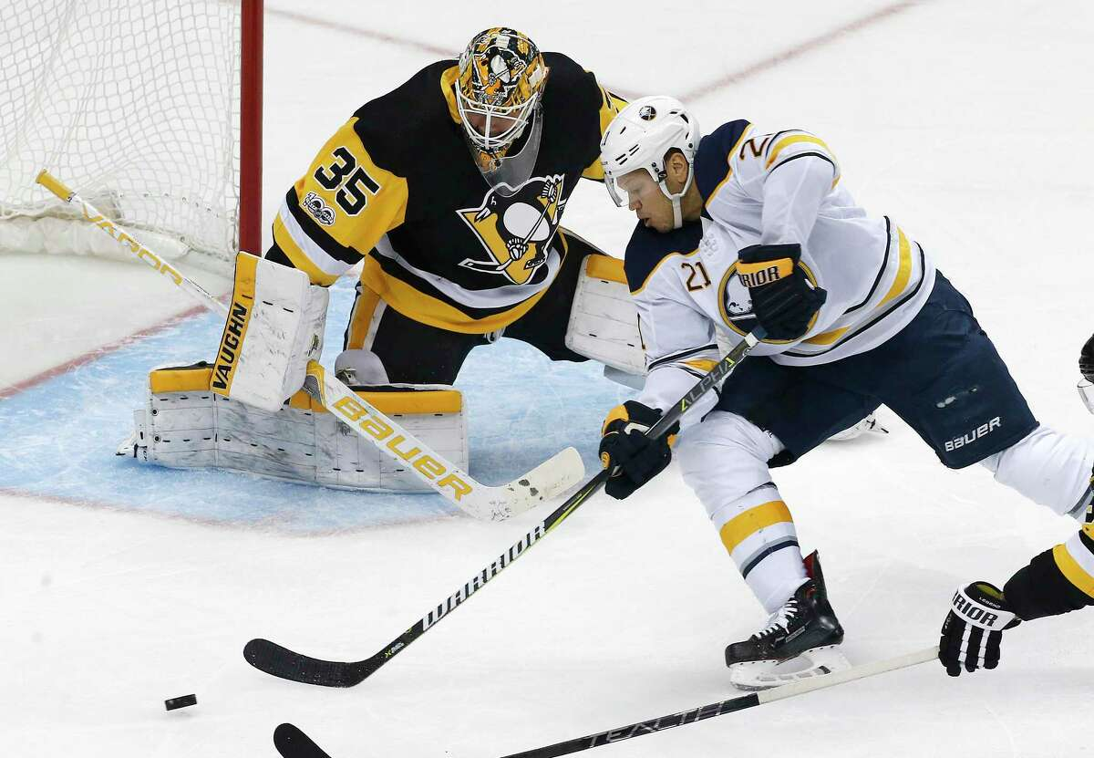 Buffalo Sabres' Kyle Okposo (21) can't get off a shot in front of Pittsburgh Penguins goalie Tristan Jarry (35) during the first period of an NHL hockey game in Pittsburgh, Saturday, Dec. 2, 2017. (AP Photo/Gene J. Puskar) ORG XMIT: PAGP104