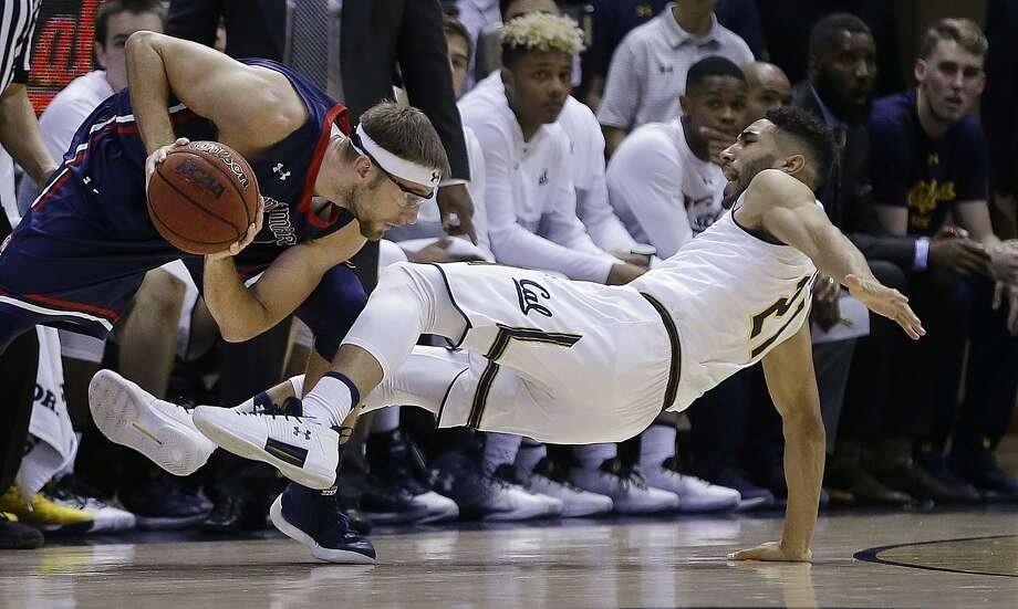 California's Nick Hamilton, right, falls to the floor after being fouled by Saint Mary's Calvin Hermanson during the first half of an NCAA college basketball game Saturday, Dec. 2, 2017, in Berkeley, Calif. (AP Photo/Ben Margot) Photo: Ben Margot, Associated Press