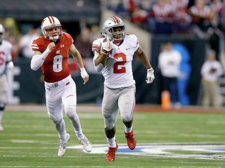 Ohio State running back J.K. Dobbins, right, runs with the ball as Wisconsin safety Joe Ferguson gives chase during the first half of the Big Ten championship NCAA college football game, Saturday, Dec. 2, 2017, in Indianapolis. (AP Photo/Michael Conroy)