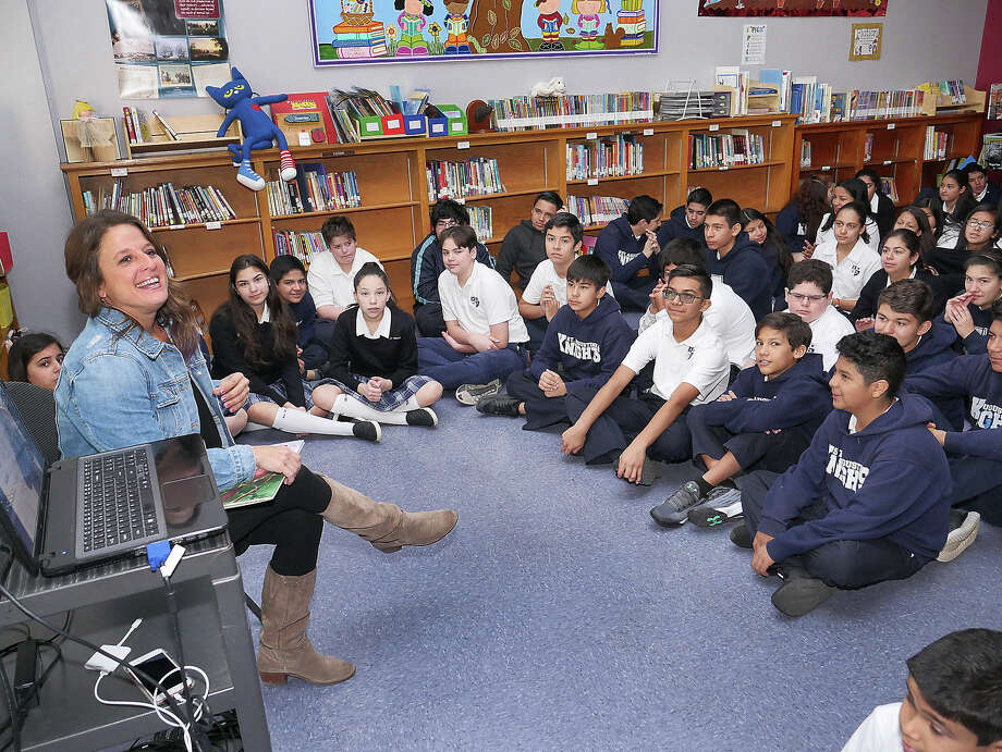 "St. Augustine High alumna and author Allison Zapata visited St. Augustine middle and elementary schools on Friday to read to them her book, ""Bernadette the Brave."" Zapata also provided a presentation for middle school students, outlining the process of writing the book. Photo: Cuate Santos/Laredo Morning Times"