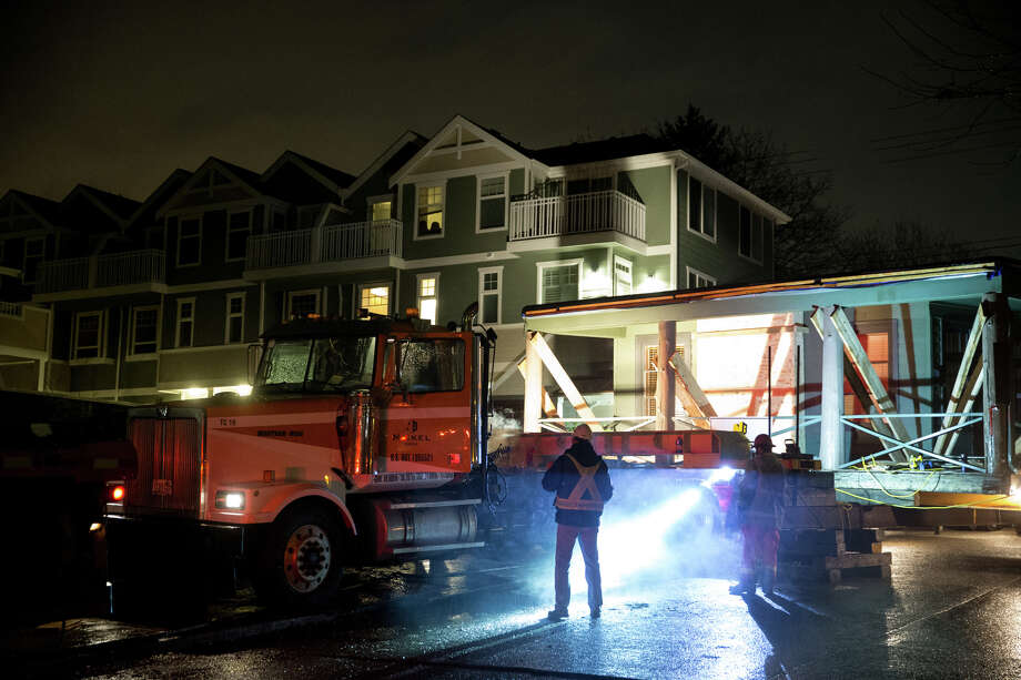 5458 California Avenue SW gets attached to a big rig before being pulled just under two miles to its new location, on Saturday, Dec. 2 ,2017. Photo: GRANT HINDSLEY, SEATTLEPI.COM / SEATTLEPI.COM