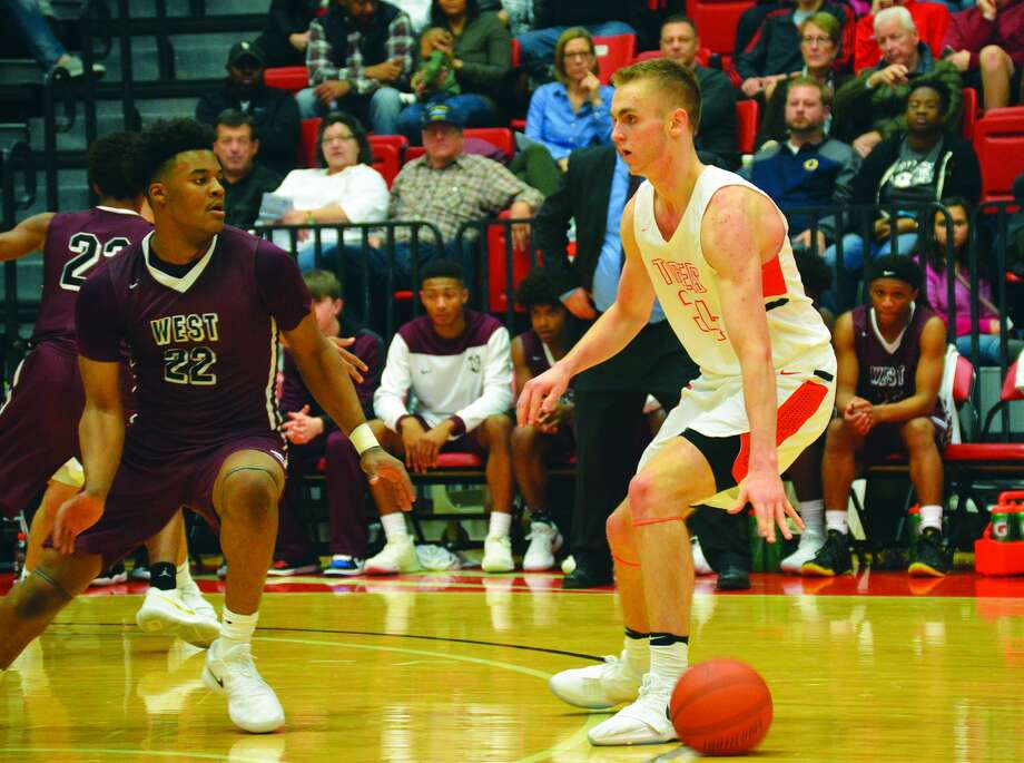Edwardsville senior Caleb Strohmeier, right, dribbles the ball at the top of the arc with Belleville West's Keith Randolph Jr. defending him in the first quarter of Saturday's game at the Vadalabene Center.