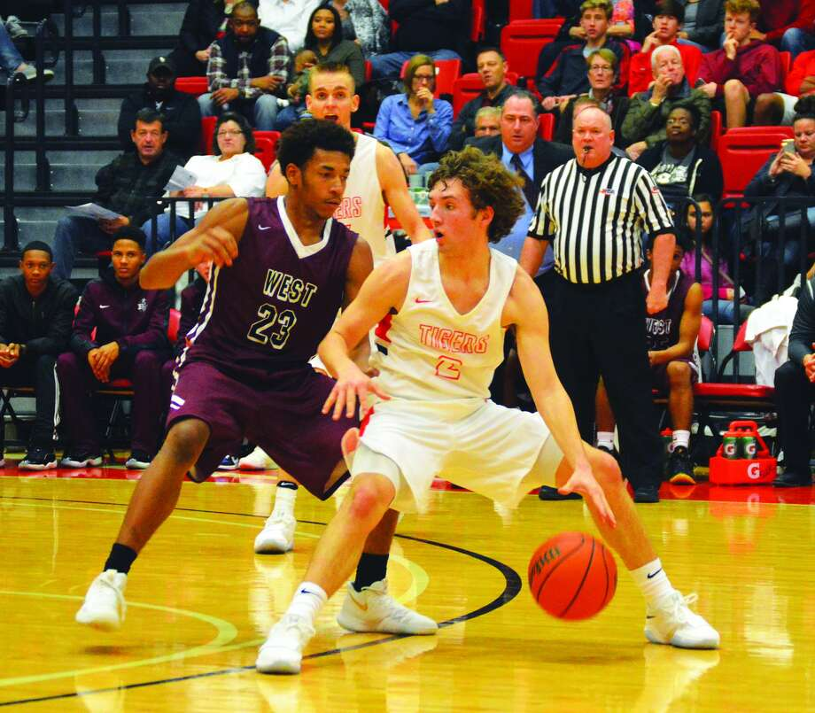 Edwardsville guard Jack Marinko, right, dribbles the ball away from Belleville West's Curtis Williams during first-half action inside the Vadalabene Center on the campus of SIUE.