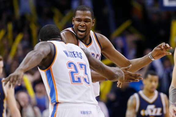 Oklahoma City Thunder forward Kevin Durant, right, celebrates with Dion Waiters (23) after Waiters hit a 3-point basket in the fourth quarter of an NBA basketball game against the Utah Jazz in Oklahoma City, Friday, Jan. 9, 2015. Oklahoma City won 99-94. (AP Photo/Sue Ogrocki)