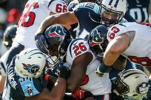 Houston Texans running back Lamar Miller (26) is stopped at the line of scrimmage by Tennessee Titans inside linebacker Avery Williamson (54) during the first quarter of an NFL football game at Nissan Stadium on Sunday, Dec. 3, 2017, in Nashville.