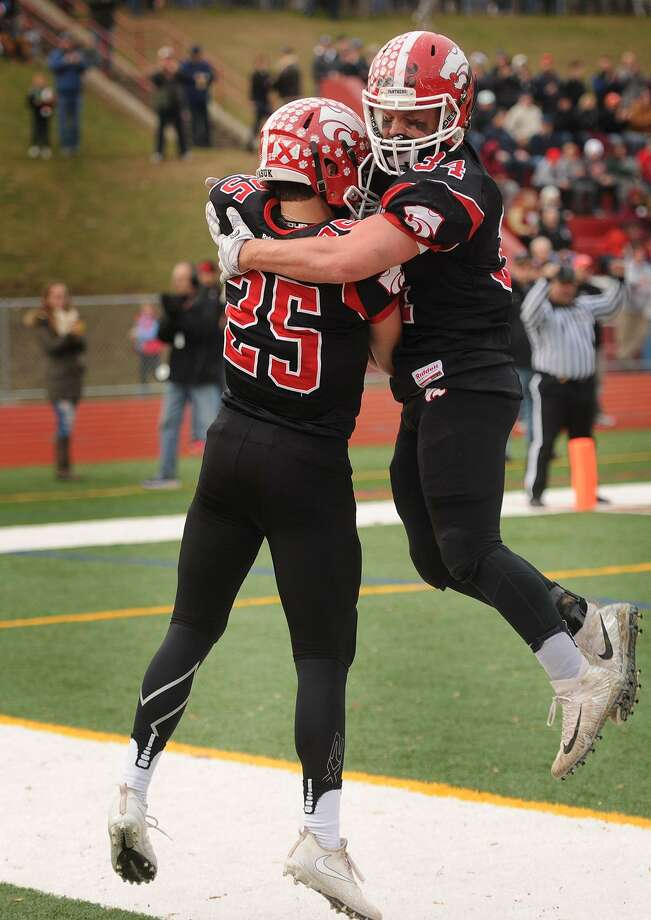 Masuk's Nicholas Lorusso, left, and Jack Roberge celebrate Lorusso's opening touchdown of the first quarter during the Panthers' Class L football semifinals victory over visiting New Canaan at Masuk High School in Monroe on Sunday. More high school football coverage, B1. Photo: Brian A. Pounds / Hearst Connecticut Media / Connecticut Post