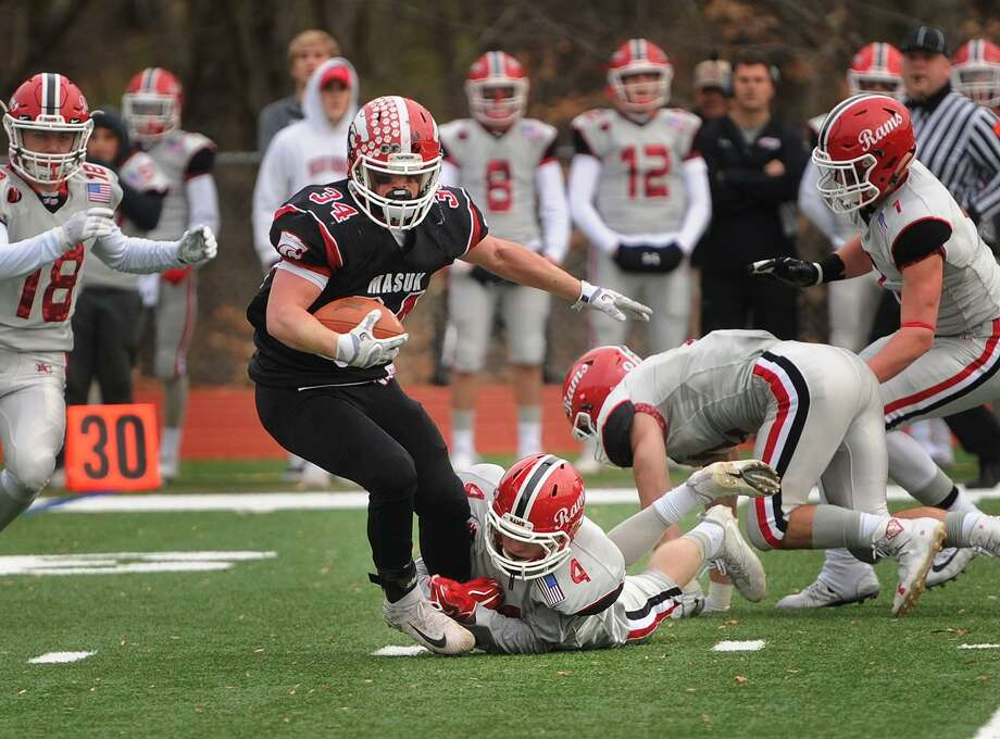 Masuk running back Jack Roberge looks to spin out of an ankle tackle by New Canaan's Zachary Miller in the first half of the Panthers' Class L football semifinals victory at Masuk High School in Monroe, Conn. on Sunday, December 3, 2017. Photo: Brian A. Pounds / Hearst Connecticut Media / Connecticut Post