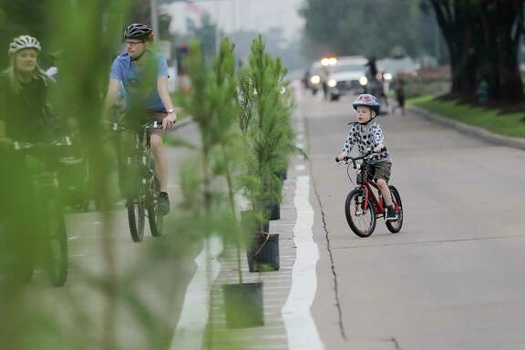 Cyclists weave in and out of trees used to divide a pop-up bike lane on  Eldridge Parkway during the last Fall 2017 Cigna Sunday Streets event on Sunday, Dec. 3, 2017, in Houston.
