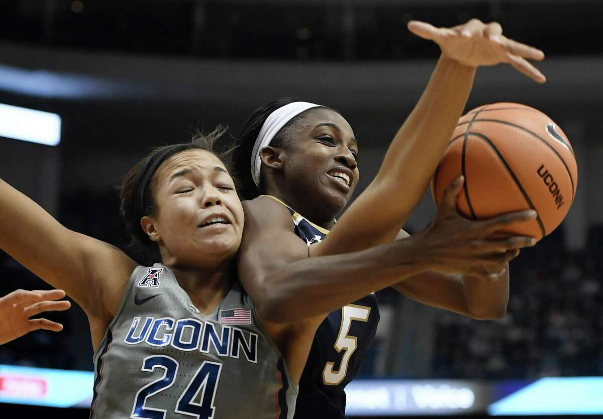 UConn's Napheesa Collier, left, tangles with Notre Dame's Jackie Young as they reach for a rebound during the first half Sunday in Hartford.