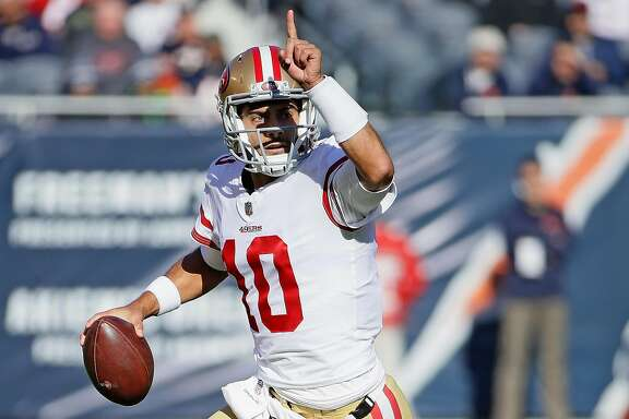 CHICAGO, IL - DECEMBER 03:   Jimmy Garoppolo #10 of the San Francisco 49ers rolls out and instructs a receiver agains the Chicago Bears at Soldier Field on December 3, 2017 in Chicago, Illinois. (Photo by Jonathan Daniel/Getty Images)