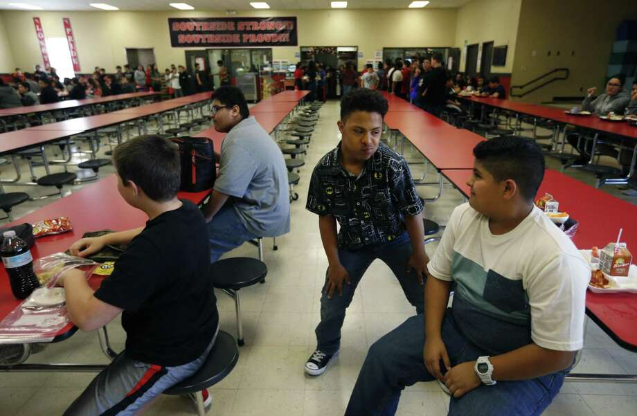 Markus Davis (center), 12, dances after having lunch with classmate Elijah Cantu (right) on Thursday, Nov. 16, 2017. Davis is deaf and entered Losoya Intermediate School in Southside ISD last year without any friends. But this year, fellow sixth-grader, Cantu, was assigned to help him. Markus taught Elijah sign language and, according to the school principal, Elijah brought Markus out of his shell. (Kin Man Hui/San Antonio Express-News) Photo: Kin Man Hui, Staff / San Antonio Express-News / ©2017 San Antonio Express-News