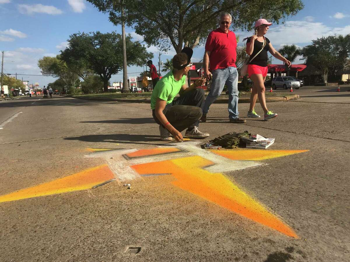 Tim Walker, 27, sketches a Houston Astros emblem in the westbound fast lane of Bellaire near Renwick during Houston Sunday Streets on Nov. 5, 2017. The event, which closed about a mile of Bellaire in the Gulfton area, was the first time the wellness initiative came to HoustonÂ?'s most diverse neighborhood.