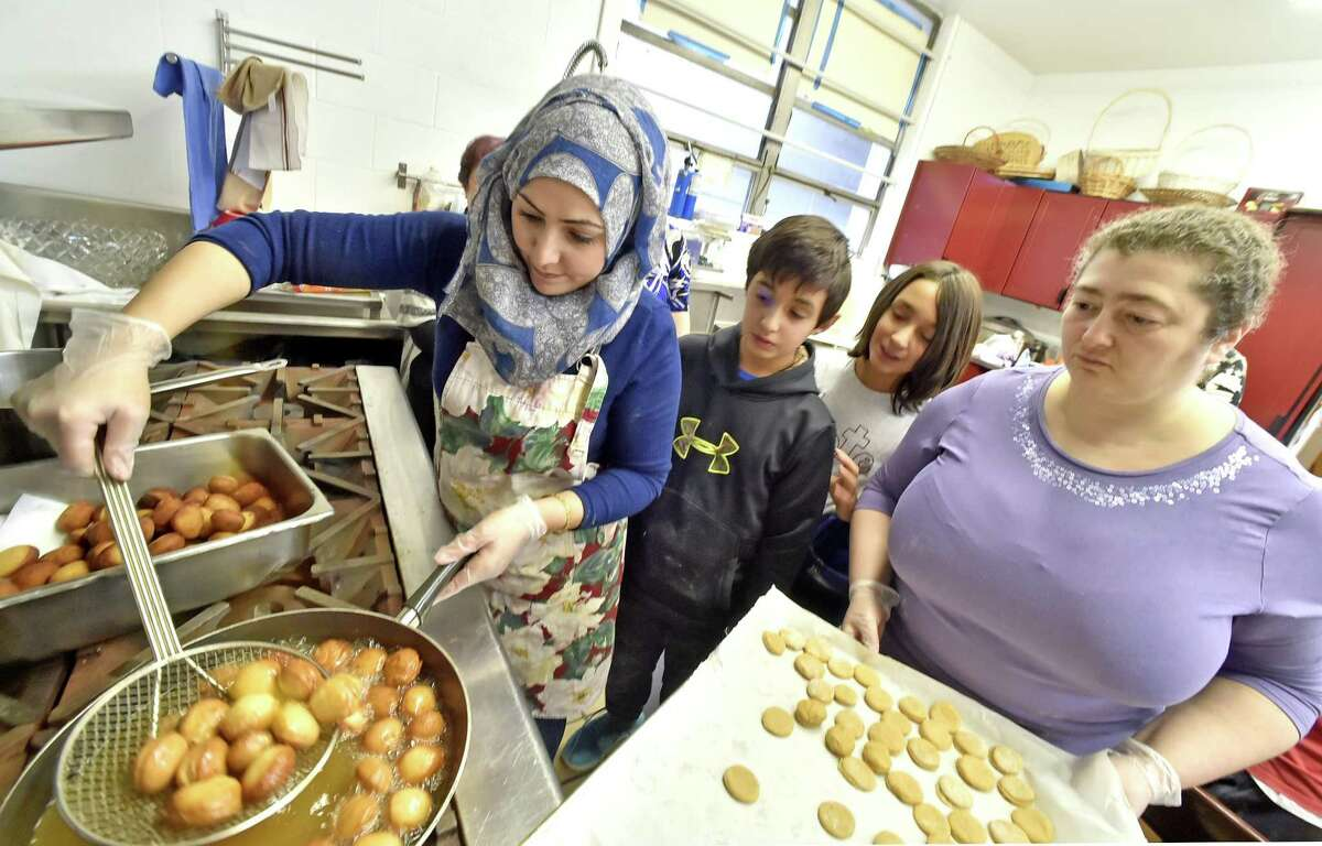 Aminah Alsaleh, left, with Elia Ahmadi, 11, of Woodbridge, twin brother Kian Ahmadi and Rachel Adelstein of New Haven watch as Alsaleh demonstrates the frying of sufganiyot.