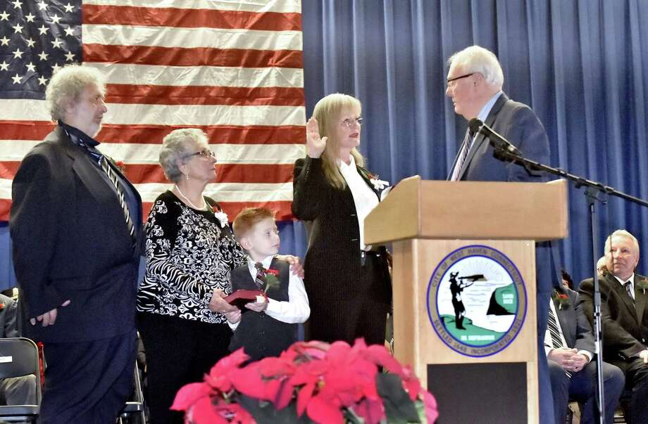 Retired Probate Judge E. Michael Heffernan, right, administers the oath of office to Nancy Rossi as the first woman mayor of West Haven Sunday. Photo: Peter Hvizdak / Hearst Connecticut Media / New Haven Register