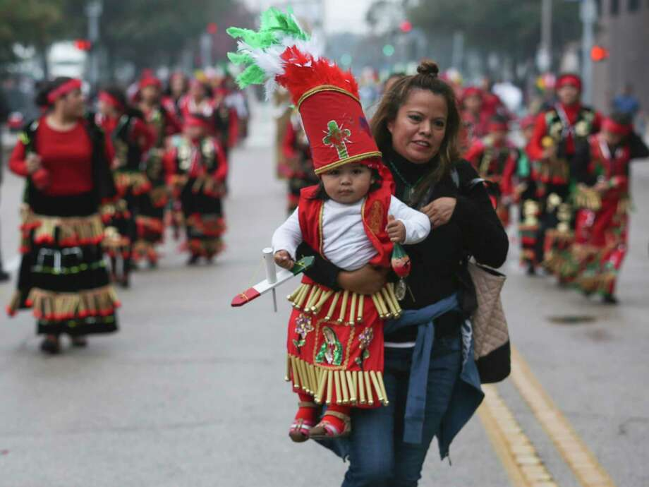 Mirna Mestizo carries her 18-month-old daughter, Guadalupe, in her arms to catch up with their group to march through downtown honoring Feast Day of Our Lady of Guadalupe on Sunday, Dec. 3, 2017, in Houston. ( Yi-Chin Lee / Houston Chronicle ) Photo: Yi-Chin Lee, Houston Chronicle / © 2017  Houston Chronicle