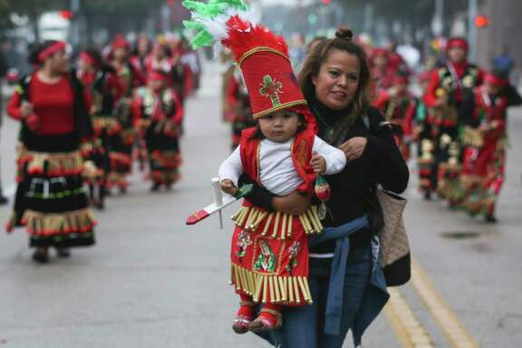 Mirna Mestizo carries her 18-month-old daughter, Guadalupe, in her arms to catch up with their group to march through downtown honoring Feast Day of Our Lady of Guadalupe on Sunday, Dec. 3, 2017, in Houston. ( Yi-Chin Lee / Houston Chronicle )