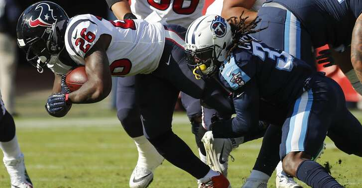 Houston Texans running back Lamar Miller (26) is stopped by Tennessee Titans strong safety Johnathan Cyprien (37) during the first quarter of an NFL football game at Nissan Stadium on Sunday, Dec. 3, 2017, in Nashville. ( Brett Coomer / Houston Chronicle )