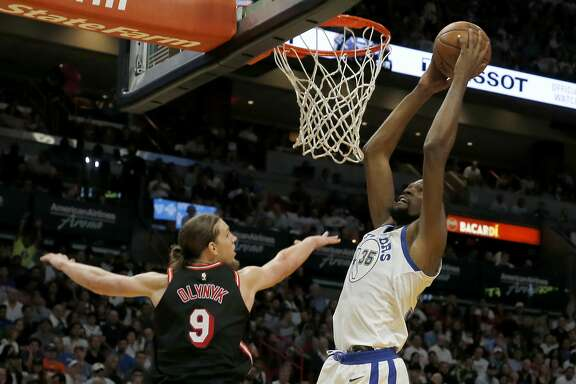 Golden State Warriors forward Kevin Durant (35) dunks next to Miami Heat center Kelly Olynyk during the first quarter of an NBA basketball game, Sunday, Dec. 3, 2017, in Miami. (AP Photo/Joe Skipper)