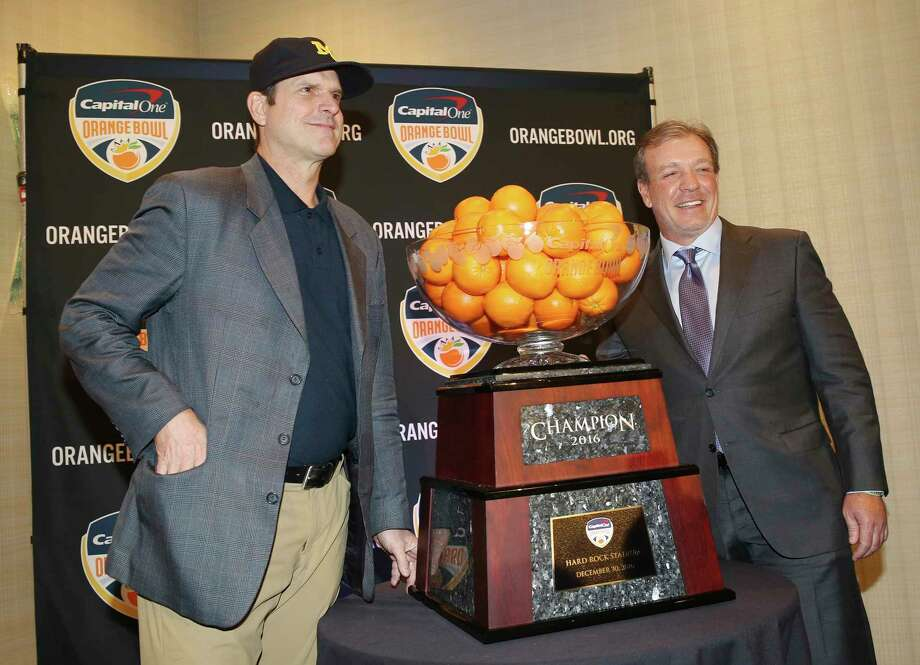 Michigan head coach Jim Harbaugh, left, and Florida State head coach Jimbo Fisher pose with the Orange Bowl trophy in Fort Lauderdale, Fla., Thursday, Dec. 29, 2016. Florida State plays Michigan in the Orange Bowl Friday. (AP Photo/Marta Lavandier) Photo: Marta Lavandier, STF / Copyright 2016 The Associated Press. All rights reserved.