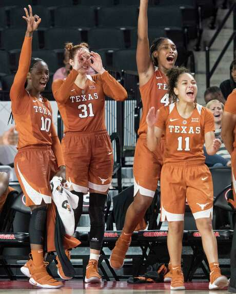 Texas' Lashann Higgs (10), Audrey-Ann Caron-Goudreau (31), Jatarie White and Brooke McCarty (11) celebrate a basket late in Sunday's win at Georgia. Photo: John Amis, FRE / FR69715 AP